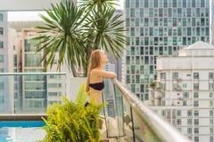 Молодая женщина в бассейне среди небоскребов и большого города Ослабьте в большом городе Остатки от стресса стоковые фотографии rf