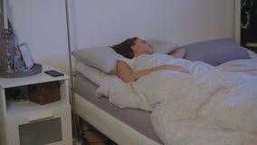 Молодая женщина в ее бодрствованиях кровати вверх в раннем утре стоковое фото