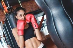 Молодая женщина в перчатках бокса в положении спортзала готовом для того чтобы пнуть грушу возбужденную стоковая фотография rf