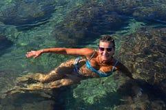 Молодая женщина в поплавках купальников стоковые изображения