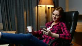 Молодая женщина в офисе имея перерыв Печатать сообщение на мобильном телефоне и выпивать кофе сток-видео