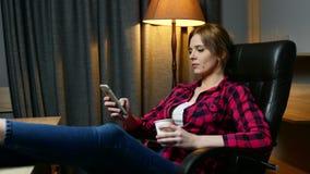 Молодая женщина в офисе имея перерыв Печатать сообщение на мобильном телефоне и выпивать кофе видеоматериал