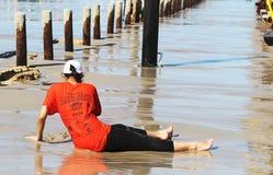 Молодая женщина играя с песком во время малой воды на пляже стоковые изображения