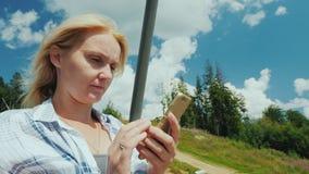 Молодая женщина использует смартфон, едет подъем лыжи на ясный летний день сток-видео