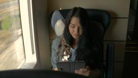 Молодая женщина используя ее планшет пока путешествующ поездом Концепция применения перемещения акции видеоматериалы