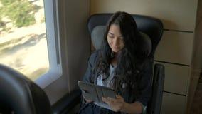 Молодая женщина используя ее планшет пока путешествующ поездом Концепция применения перемещения сток-видео