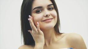 Молодая женщина крупного плана счастливая прикладывая сливк к ее стороне Skincare и концепции косметик Косметика Забота кожи стор акции видеоматериалы