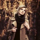 Молодая женщина моды в бежевом пальто идя в парк осени стоковые фотографии rf