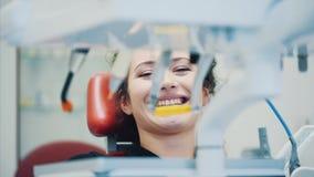 Молодая женщина на встрече дантиста В течение этого периода он сидит на зубоврачебном красном стуле Во время этого задушевно усме сток-видео