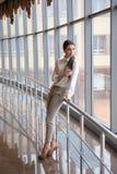 Молодая женщина на международном аэропорте Женский пассажир на стержне, внутри помещения стоковое изображение