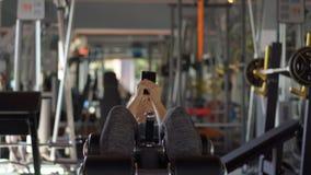 Молодая женщина на спортзале трясет прессу держа телефон перед ее глазами в ее руках Полностью внимание внутри сток-видео