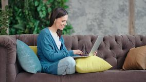 Молодая женщина полной съемки усмехаясь случайная используя текст ПК ноутбука печатая сидя на уютном кресле видеоматериал