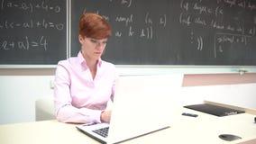 Молодая женщина подготавливает уча урок в классе на ее компьютере акции видеоматериалы