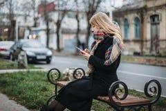 Молодая женщина портрета красивая на стенде в городской предпосылке смотря телефон стоковые изображения rf