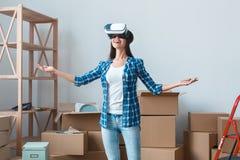 Молодая женщина двигая к новому положению места смотря в усмехаться шлемофона виртуальной реальности возбужденный стоковое фото rf