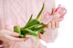 Молодая женщина держа розовые тюльпаны на белой предпосылке стоковое фото