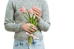 Молодая женщина держа розовые тюльпаны на белой предпосылке стоковое фото rf