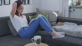 Молодая женщина сидит на кресле с планшетом стоковое изображение rf