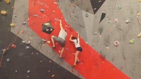 Молодая женщина сделала успех на стене скалолазания сток-видео
