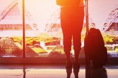 Молодая женщина стоит около окна в аэропорте стоковая фотография