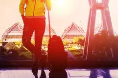 Молодая женщина стоит около окна в аэропорте стоковое изображение rf