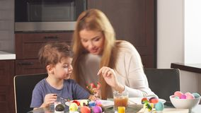 Молодая женщина с ее прелестным маленьким сыном делая handmade украшения на праздник пасхи видеоматериал