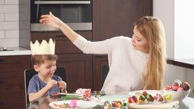 Молодая женщина с ее прелестным маленьким сыном делая handmade украшения на праздник пасхи сток-видео