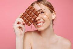 Молодая женщина с чистой кожей держа черный бар шоколада в ее руках, закрывая один глаз с шоколадом на розовой предпосылке стоковые изображения