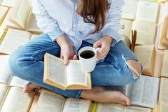 Молодая женщина читает книгу и кофе напитков Концепция на день книги мира, образ жизни, исследование, образование стоковые изображения rf