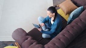 Молодая женщина хипстера взгляда сверху усмехаясь ослабляя на кресле используя ПК планшета сток-видео