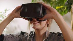 Молодая женщина регулируя изумленные взгляды виртуальной реальности и кладя их дальше видеоматериал
