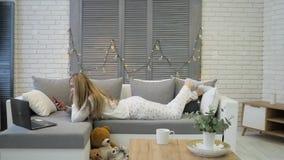 Молодая женщина со смартфоном и ноутбук лежа на софе дома акции видеоматериалы