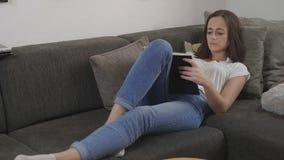 Молодая женщина ослабляет в живущей комнате пока читающ книгу стоковое изображение