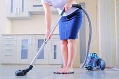 Молодая женщина очищает квартиру В руках бытового прибора, пылесос Концепция чистоты и стоковая фотография rf