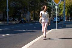 Молодая красивая женщина брюнета идя на улицу стоковое изображение