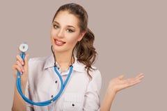 Молодая красивая женщина доктора усмехаясь над серой предпосылкой Стетоскоп стоковое изображение