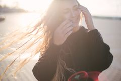 Молодая красивая женщина с длинными танцами вьющиеся волосы и наслаждаться солнечным светом стоковая фотография