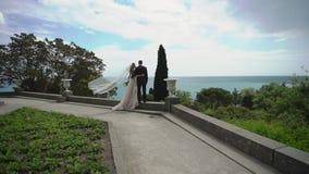 Молодая красивая невеста в платье свадьбы и выхолить обнимать и целовать видеоматериал