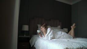 Молодая красивая девушка в кофе купального халата выпивая на утре видеоматериал