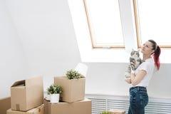 Молодая красивая девушка с покрашенными волосами в белой футболке и джинсах, держа кота любимца и смотря вне окно стоковое фото
