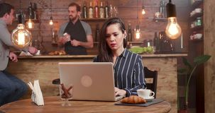 Молодая, красивая сфокусированная женщина пишущ текст на ее деятельности ноутбука от ресторана акции видеоматериалы