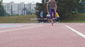 Молодая красивая тренировка спортсмена девушки бежать быстрое начало на стадионе атлетики города во время тренировки дня в медлен акции видеоматериалы