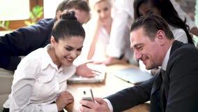 Молодая команда деловых партнеров подготавливает для важной встречи в солнечном конференц-зале видеоматериал