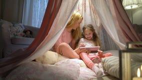 Молодая мать и ее дочь имея потеху используя планшет играя приложения сток-видео