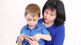 Молодая мать и ее сын играют смартфон и усмехаются, на белой предпосылке сток-видео