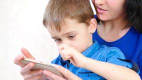 Молодая мать и ее сын играют смартфон и усмехаются, на белой предпосылке акции видеоматериалы