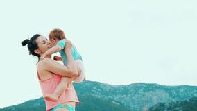Молодая мать с ее маленьким ребенком имеет потеху на пляже в летнем дне видеоматериал