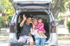 Молодая мусульманская семья, переход, отдых, концепция поездки и людей - счастливый человек, женщина и маленькая девочка сидя на  стоковые изображения rf
