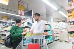 Молодая пара стоит в середине супермаркета Девушка смотрит список товаров в ее смайлике стоковое изображение rf