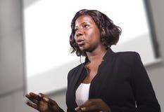 Молодая привлекательная и уверенная черная Афро-американская бизнес-леди со шлемофоном говоря в аудитории на корпоративной тренир стоковые фотографии rf